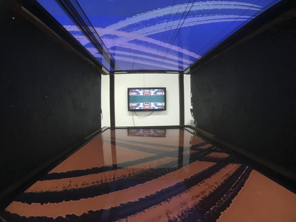 Two opposing TV damaged screens showing videos. Art installation